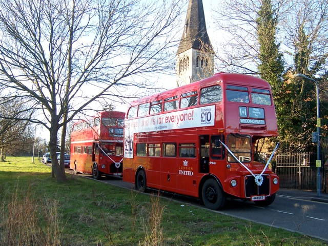 Photo of two Routemaster buses in a wedding procession outside a church in London